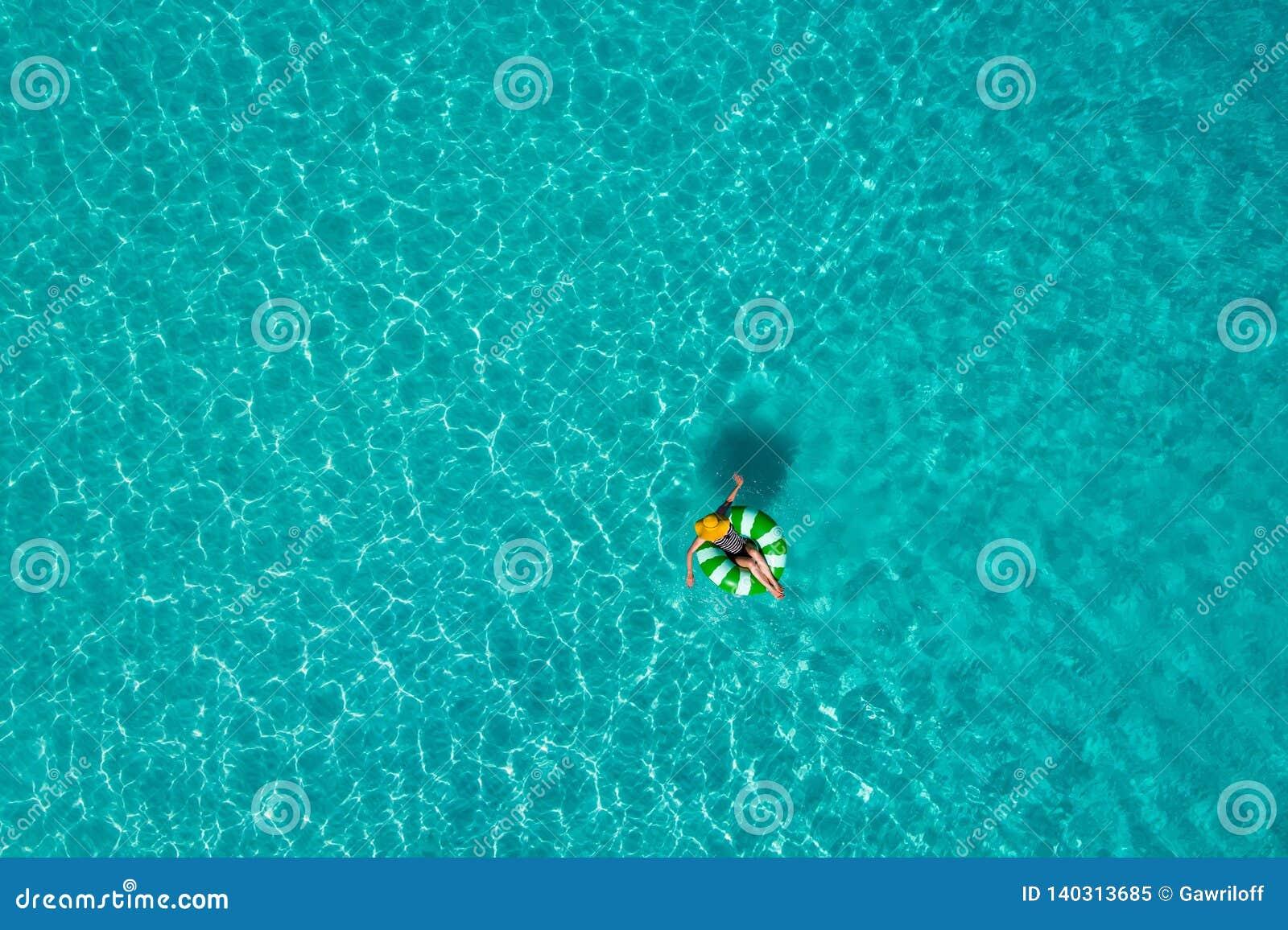 微小的妇女游泳鸟瞰图在游泳圆环多福饼的在透明绿松石海在塞舌尔 夏天海景与