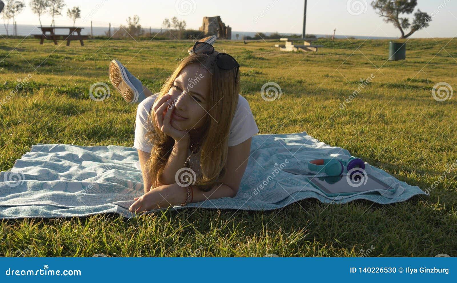 心情的年轻女人在公园和梦想放置
