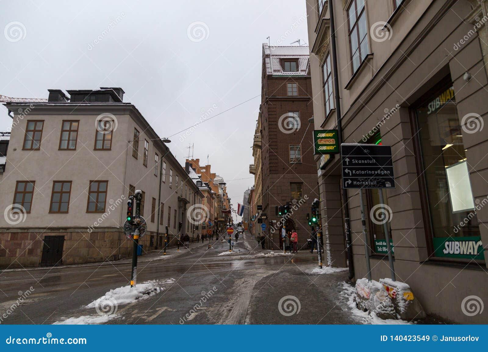 城市的斯德哥尔摩瑞典,街道视图有熔化的雪的和轻的交通