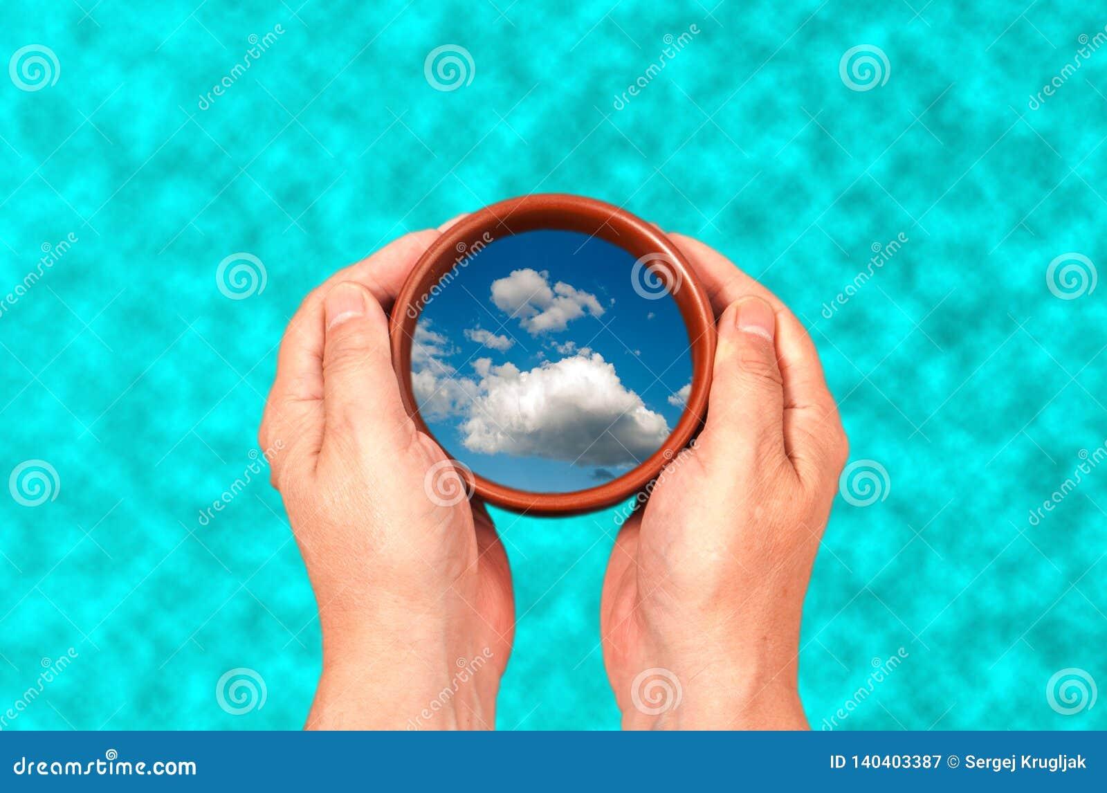 在一个杯子的手上有云彩的反射的在水背景的
