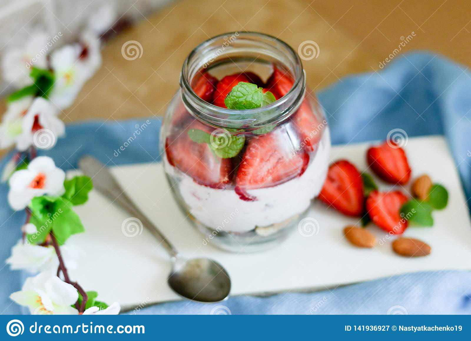 在一个瓶子的五颜六色的水果沙拉在白色和蓝色土气木背景 顶视图 在瓶子的草莓奶昔
