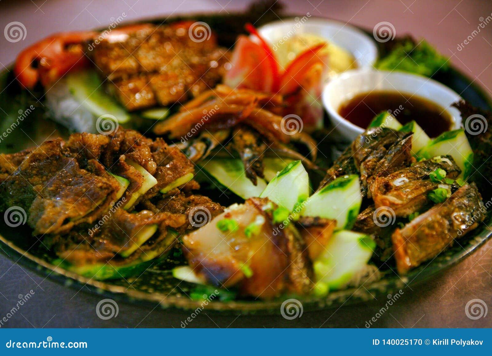 在一块板材的鱼盛肉盘有菜的在中国料理店,广州