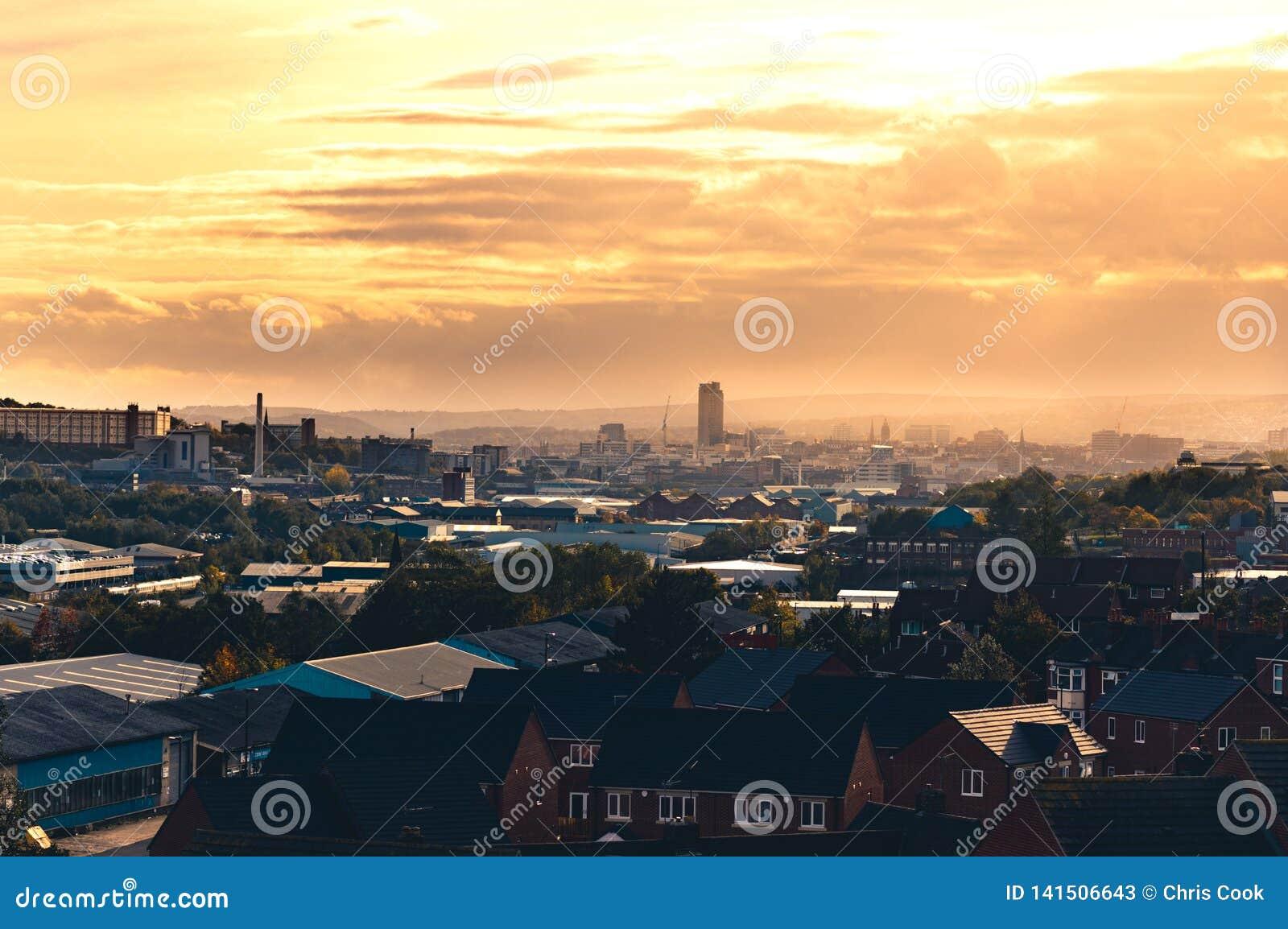 在云彩后的温暖的橙色日落在谢菲尔德,南约克郡,英国