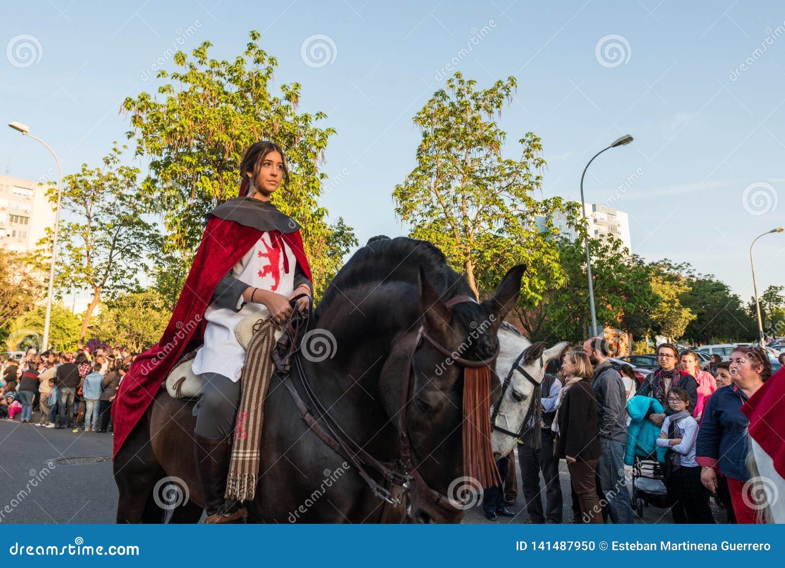 在她的马的一个年轻车手在中世纪礼服在圣乔治和龙的庆祝时