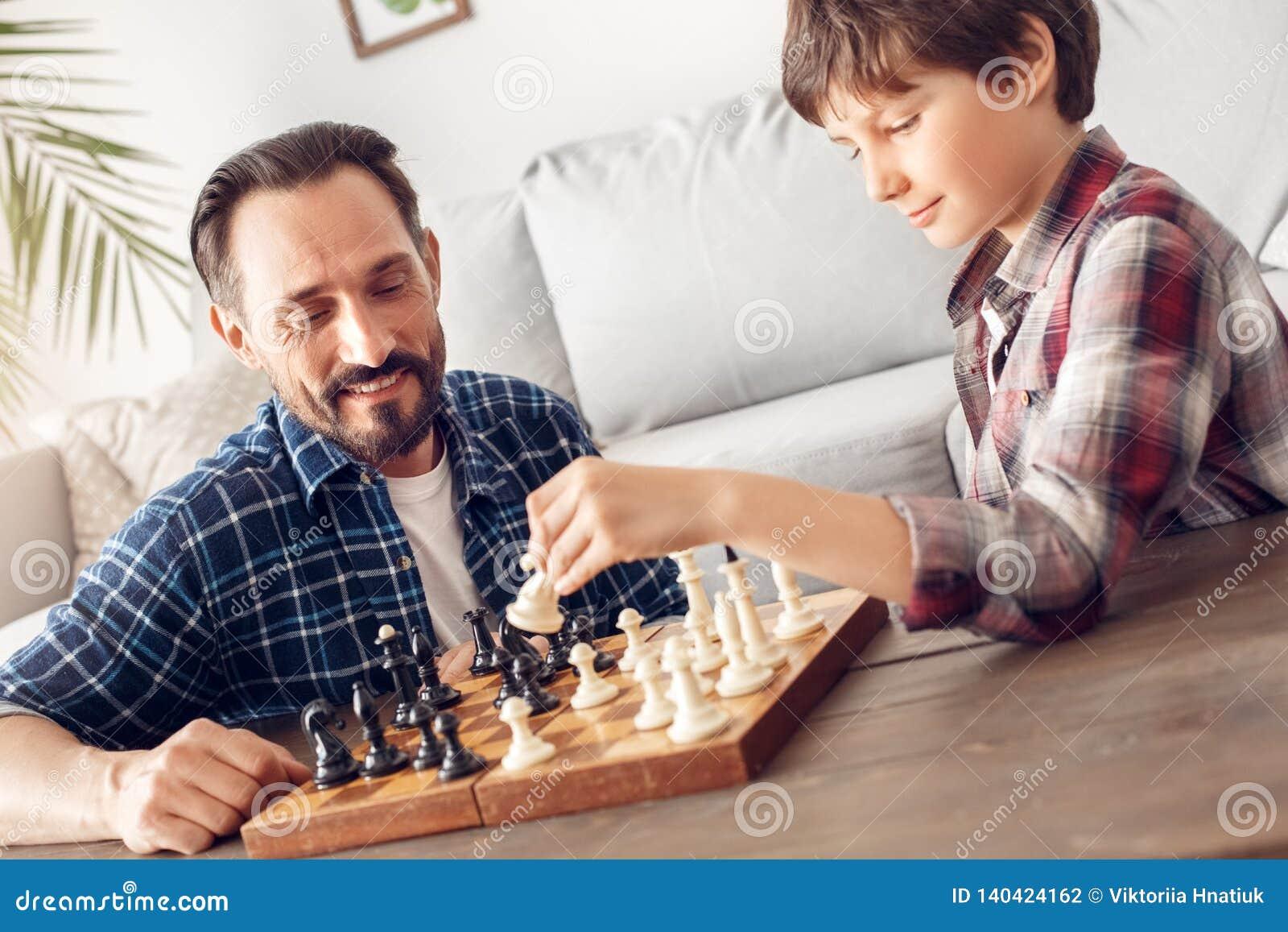 在家坐在桌上的父亲和一点儿子演奏看ceerful男孩藏品骑士的棋爸爸体贴