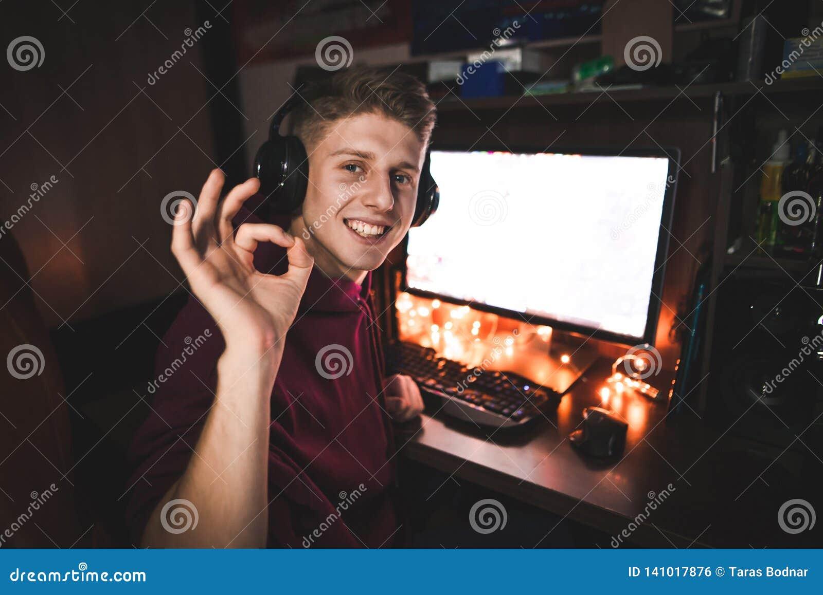 在家打电子游戏在晚上,微笑和显示姿态OK的一愉快的年轻人的画象