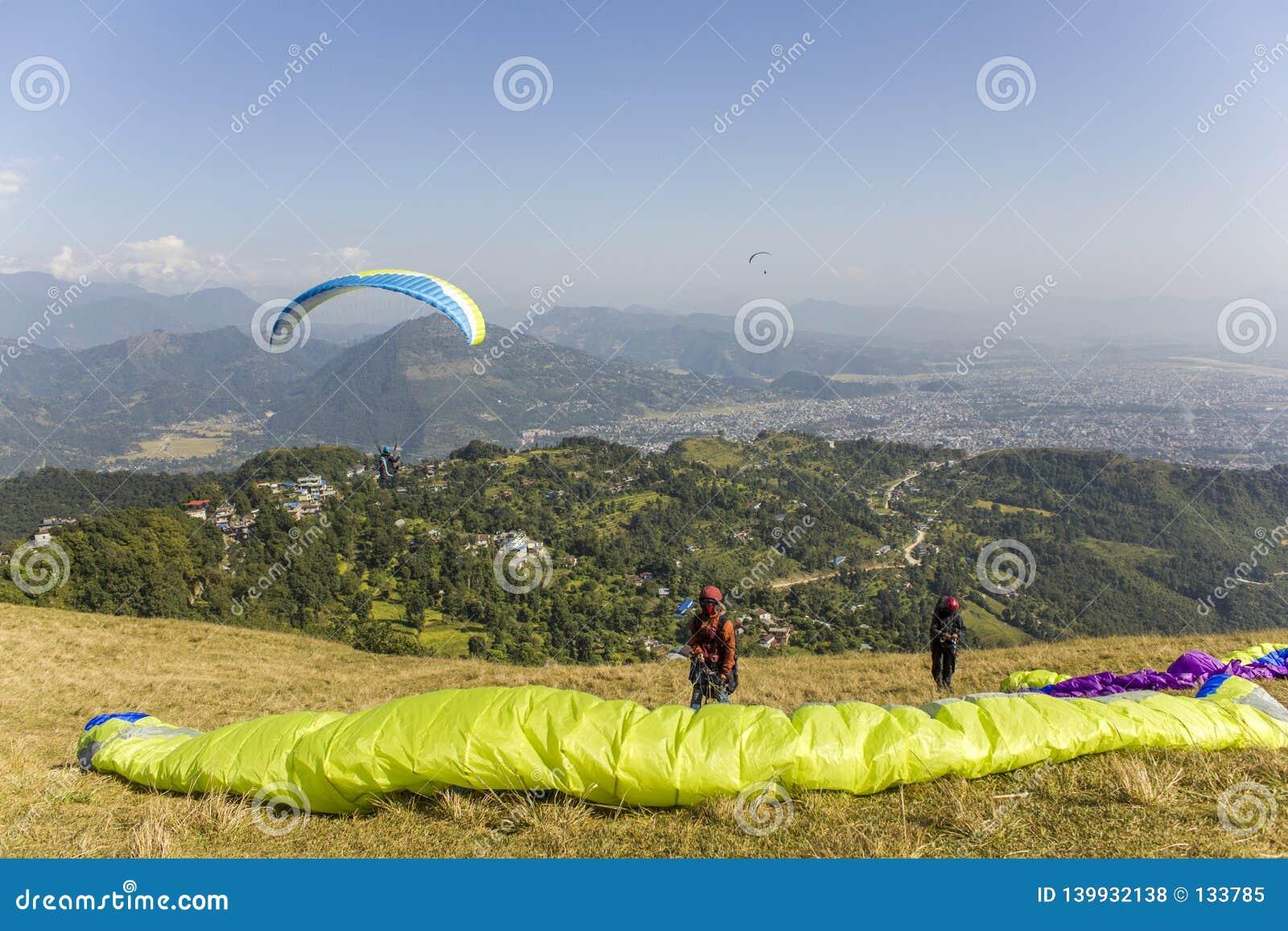 在山坡的两个滑翔伞在离开反对山谷的背景和飞行前
