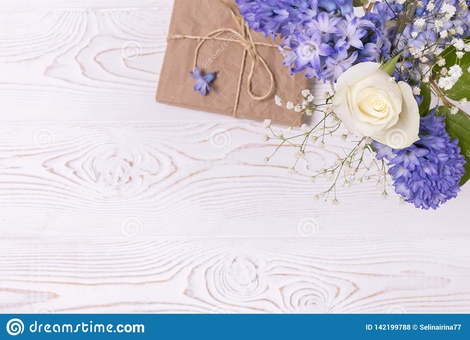 在工艺纸和蓝色风信花花包裹的礼物盒,在白色台式的白玫瑰 平的位置 复制空间为