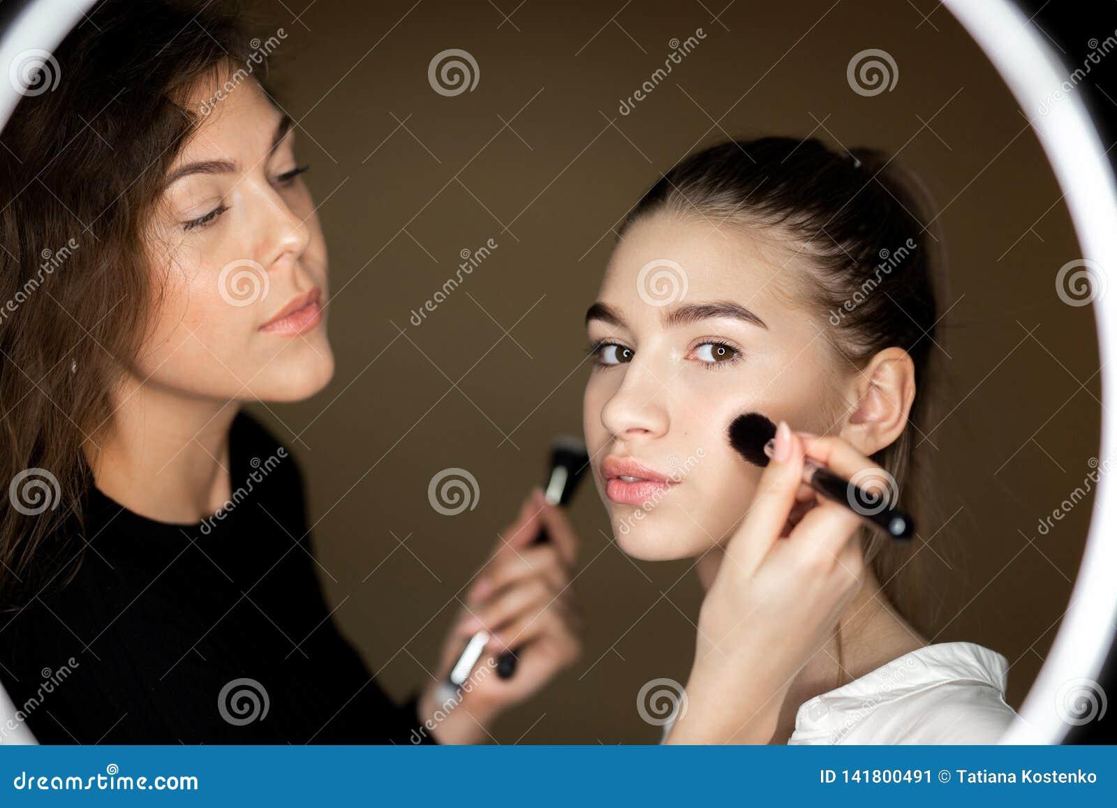 在化妆师镜子的反射迷人的女孩对构成做一美丽的少女