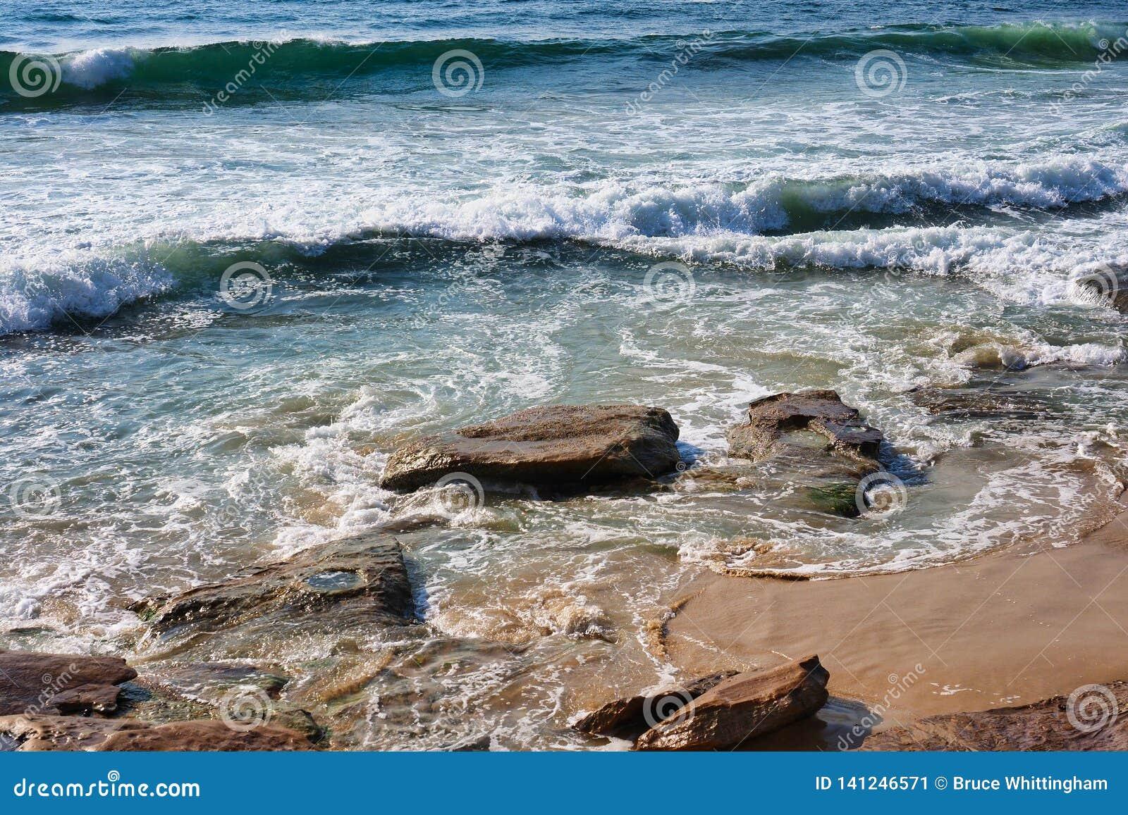 在克罗纳拉海滩岩石和沙子,悉尼,澳大利亚的太平洋波浪