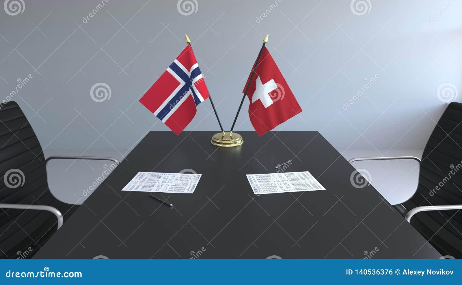 在桌上的挪威和瑞士的旗子和纸 交涉和签署一项国际协定 概念性