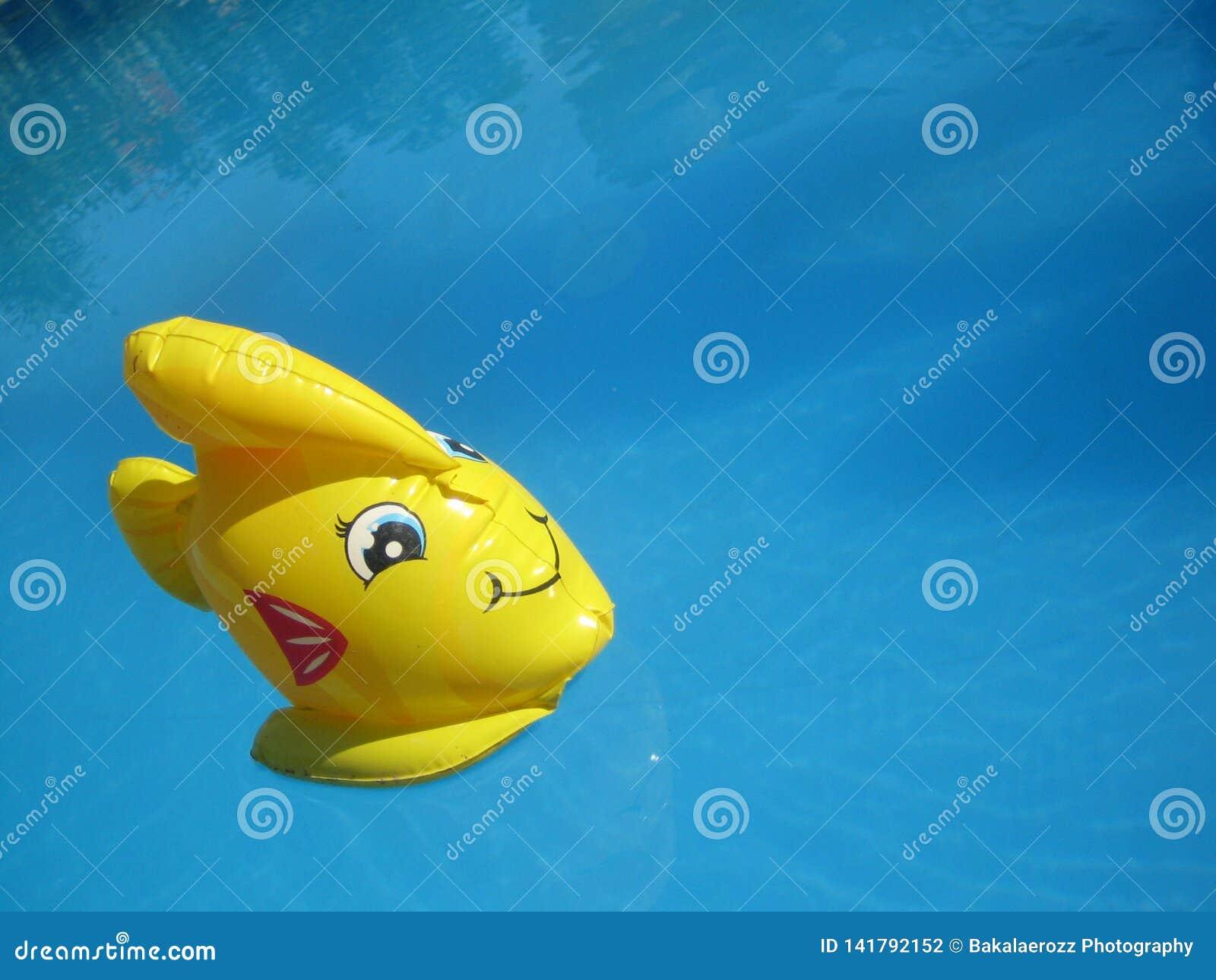 在深蓝色游泳场水宏观墙纸的惊人的黄色玩具鱼