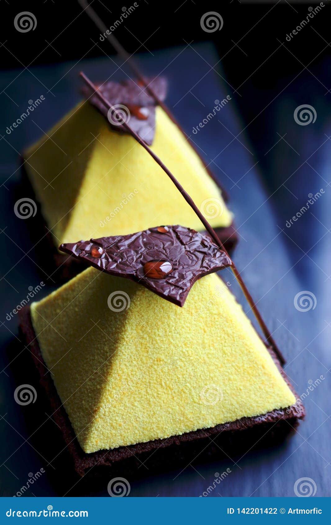 在果仁巧克力黑暗的背景的黄色金字塔点心