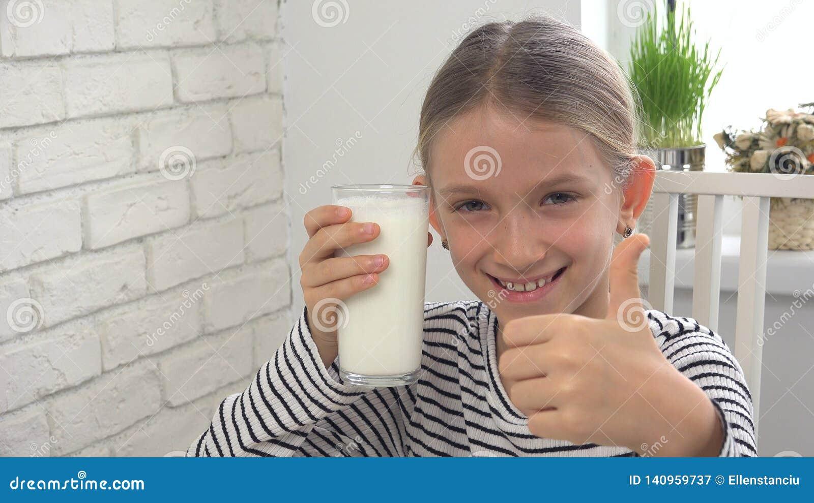 在早餐的儿童饮用奶在厨房,女孩品尝乳制品里