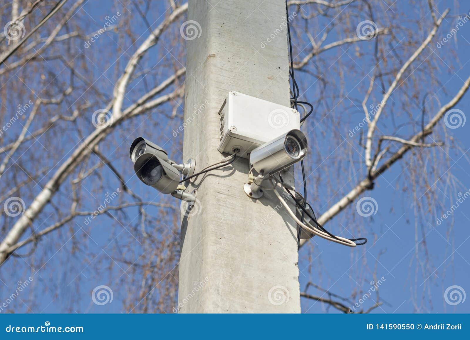 在支持岗位的紧凑录影监视器在天空蔚蓝的公开区域 在杆的安全监控相机