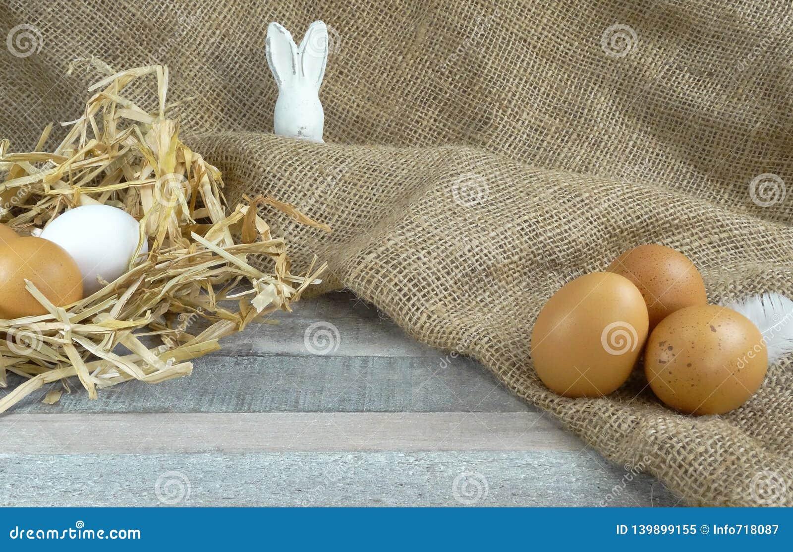 在秸杆巢witheaster兔宝宝的鸡鸡蛋在木背景的粗麻布