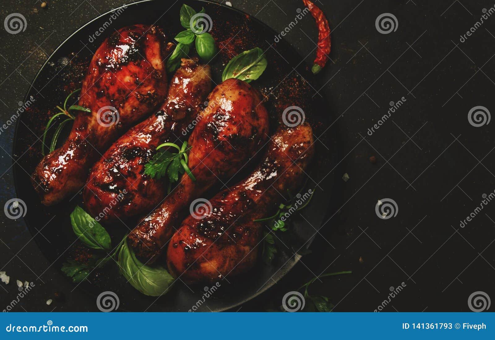在辣釉的被烘烤的鸡腿用在板材的蜂蜜调味汁,黑厨房用桌背景,亚洲食物,顶视图
