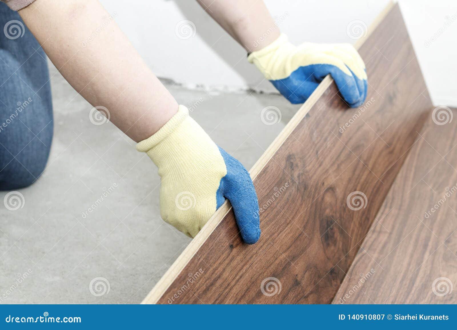 在蓝色手套的大师做放置 地板 有水平 并且橡胶锤子