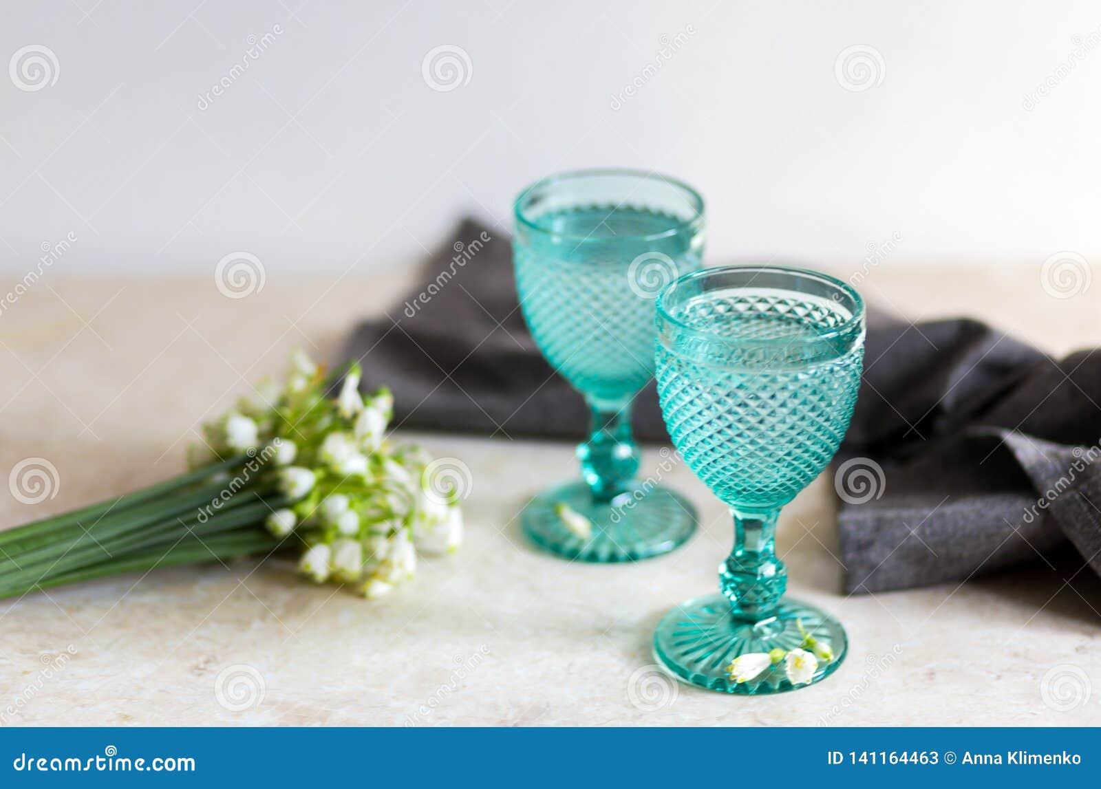在蓝色葡萄酒觚的Refhesing饮料在与srping的花的白色背景