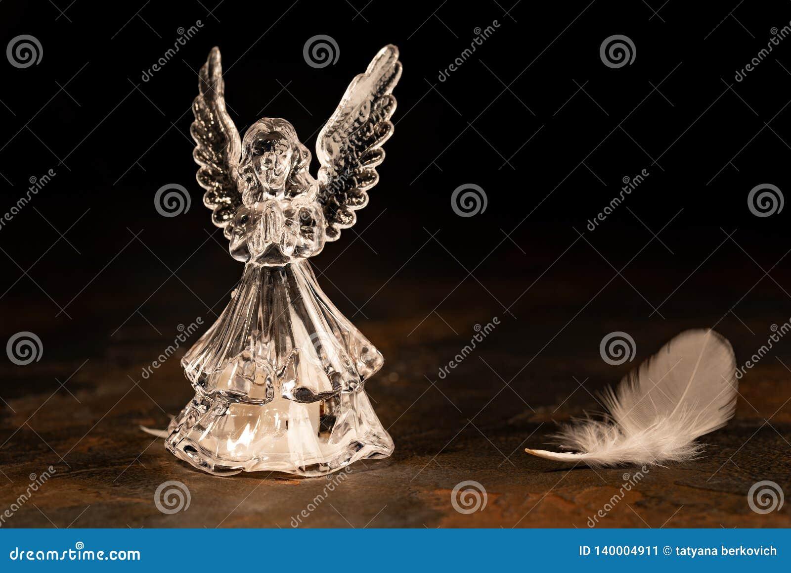 在黑暗的背景的玻璃天使