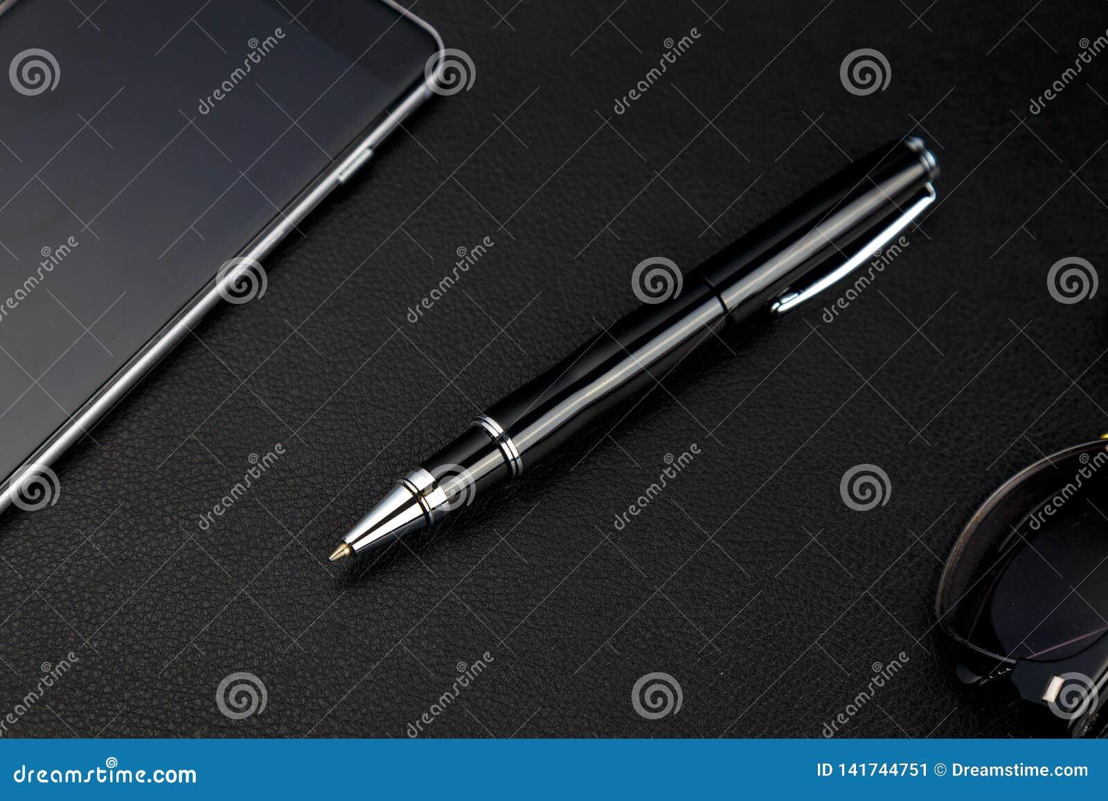 在黑背景的球发光的金属笔 豪华点笔特写镜头