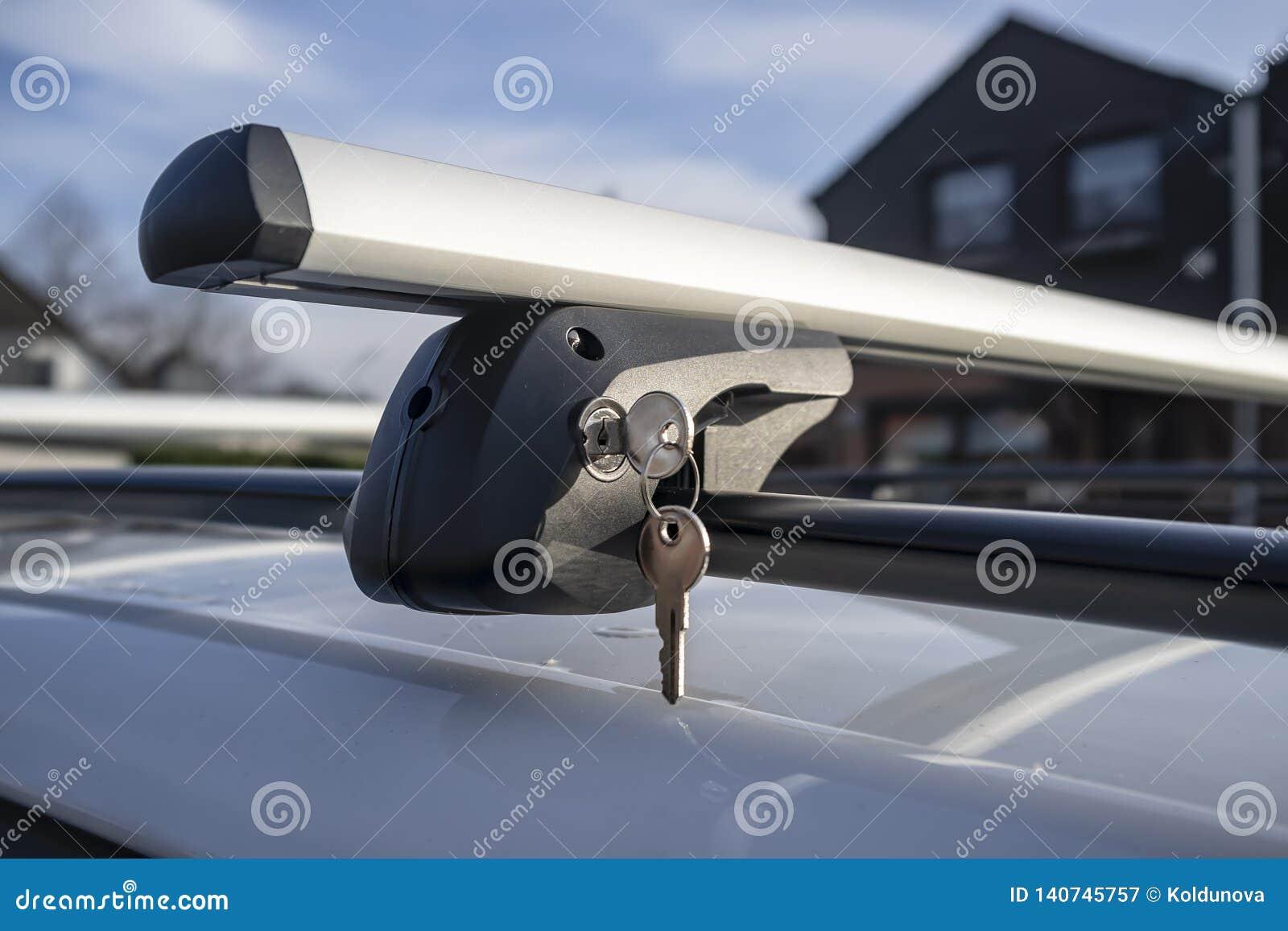 在锁的钥匙紧固车厢或货物箱子的持有人到车屋顶,在一个晴朗的春日反对天空蔚蓝