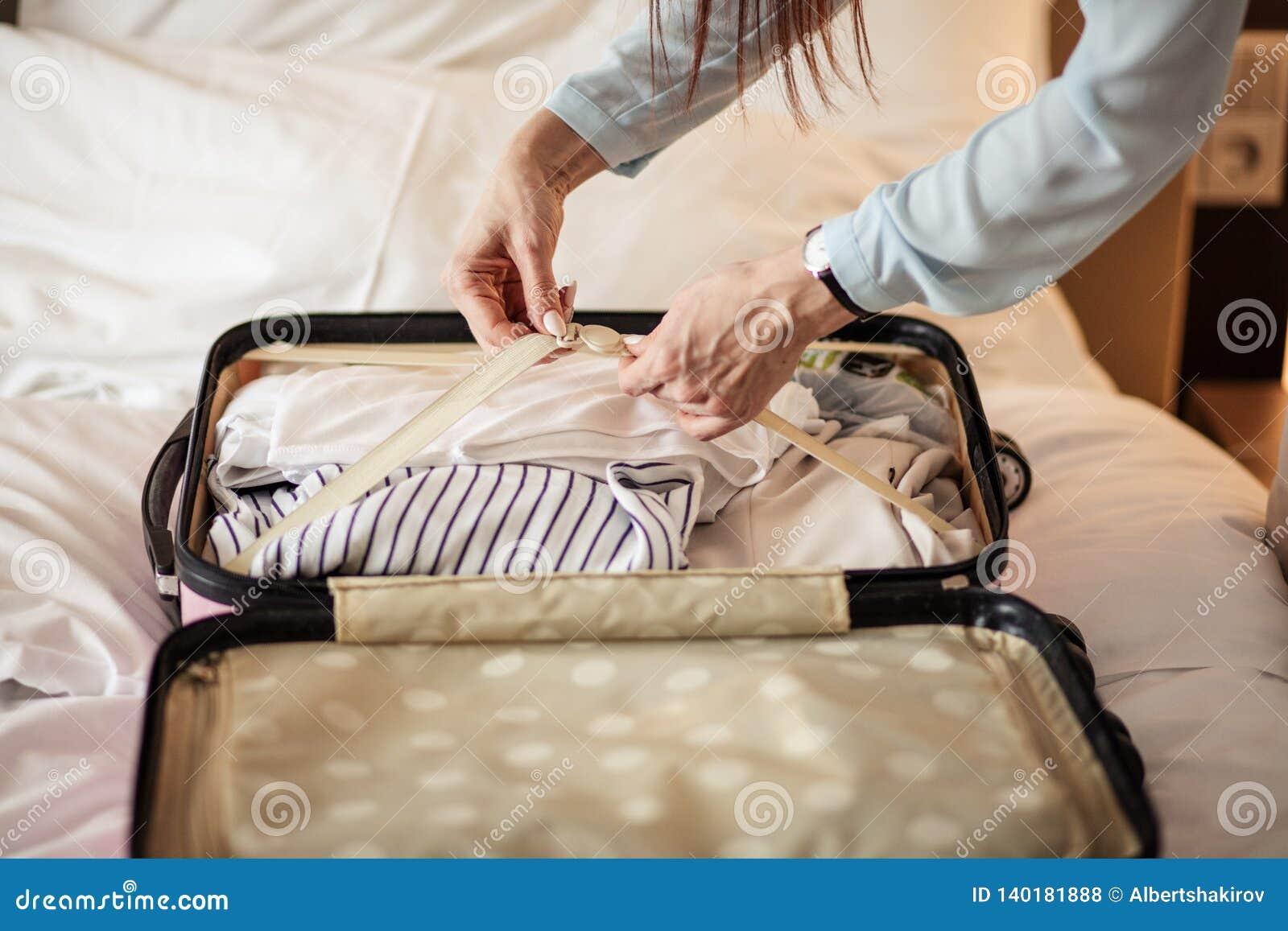 包装事的典雅的衣裳的妇女入旅行包,离开旅馆