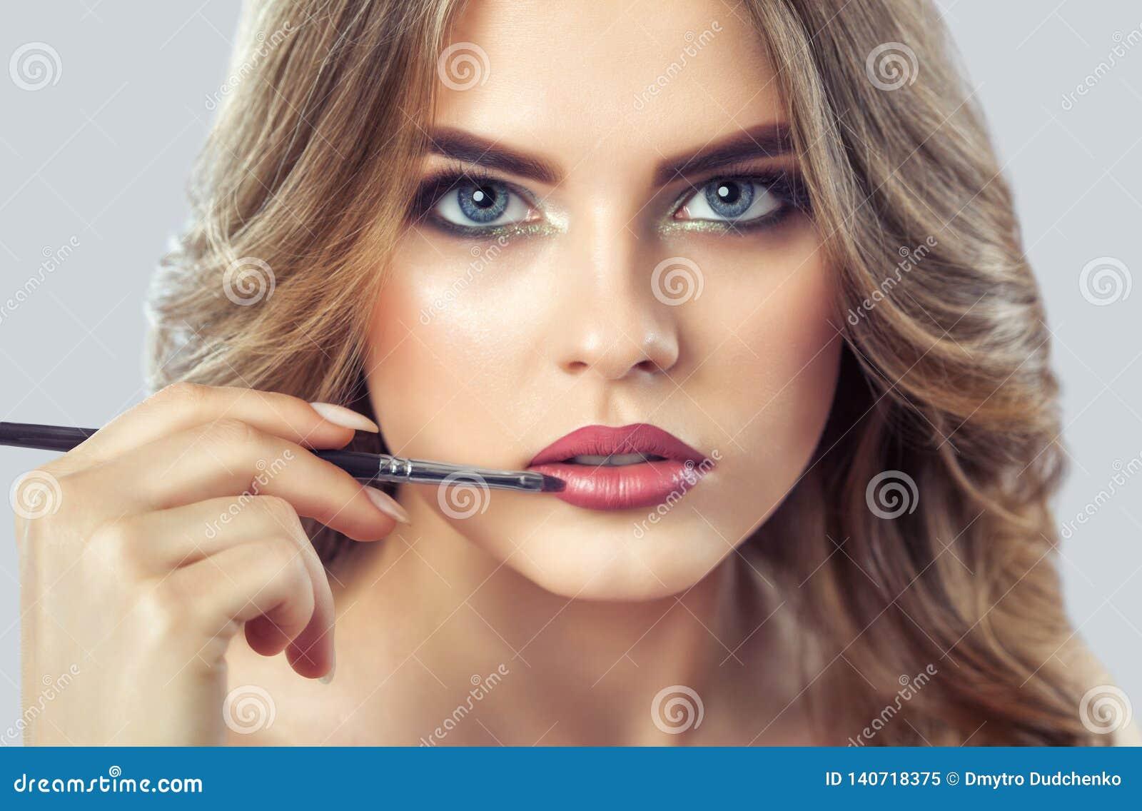 化妆师绘美女的嘴唇,完成在发廊的构成