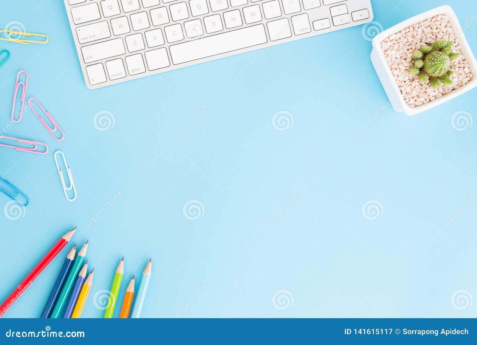 办公桌平的被放置的照片有铅笔和键盘的,在蓝色背景的顶视图workpace和拷贝空间