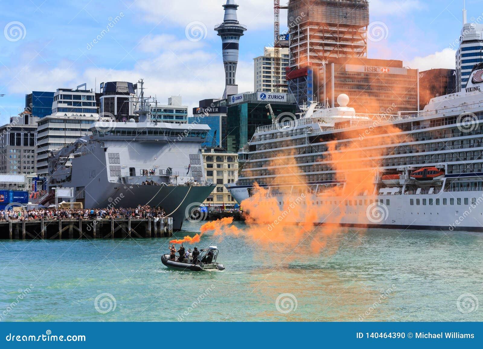 Łódź demonstruje pomarańczowego morskiego racę w Auckland schronieniu, Nowa Zelandia