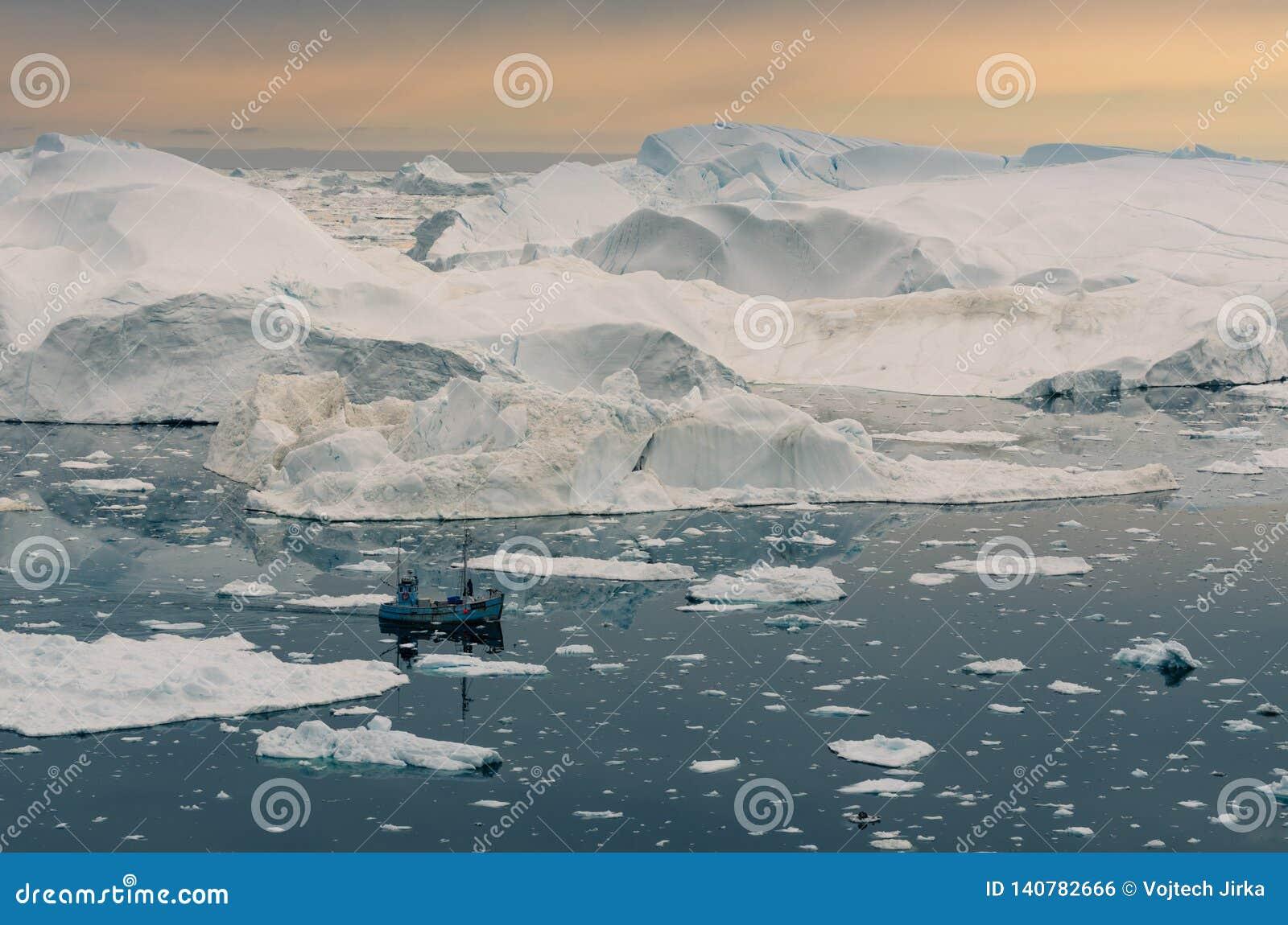 Łódkowaty żeglowanie wśród ogromnych gór lodowych w Ilulissat icefjord, Greenland