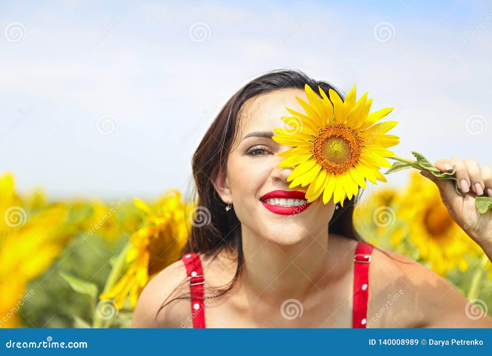 Ładna brunetki kobieta w słonecznika polu