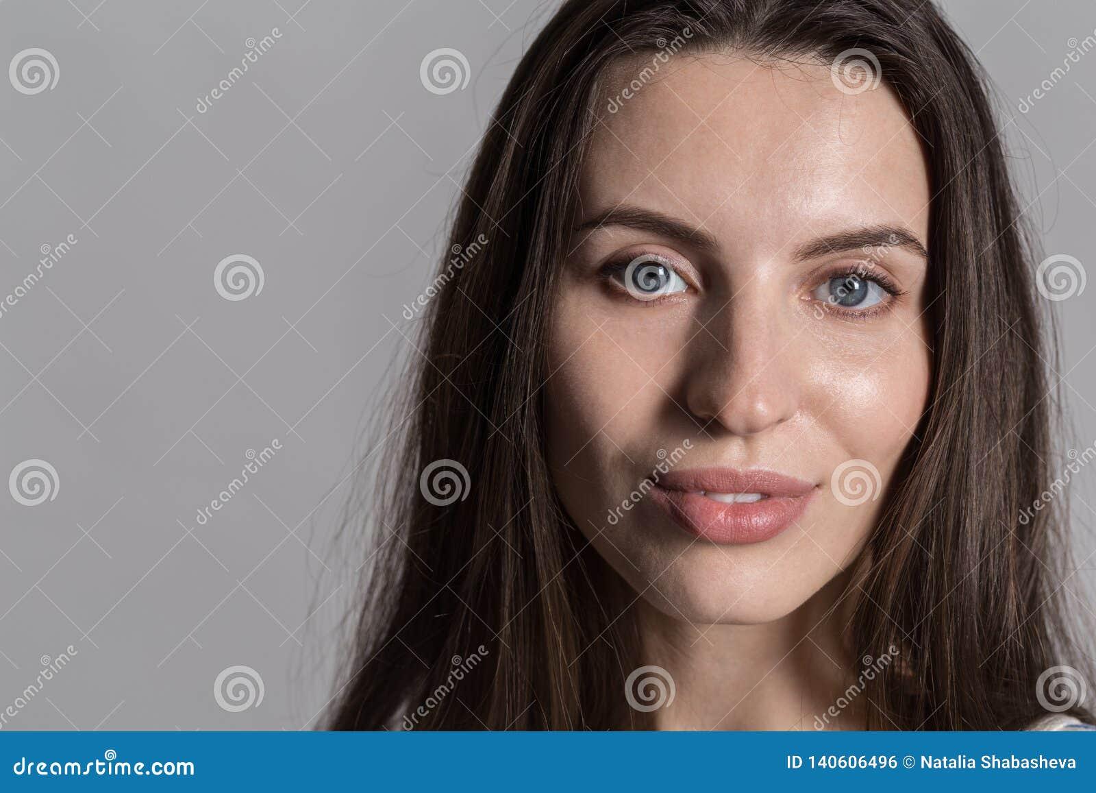 Ładna kobieta z puszystym włosy, ubierającym niezobowiązująco przeciw szarej studio ścianie