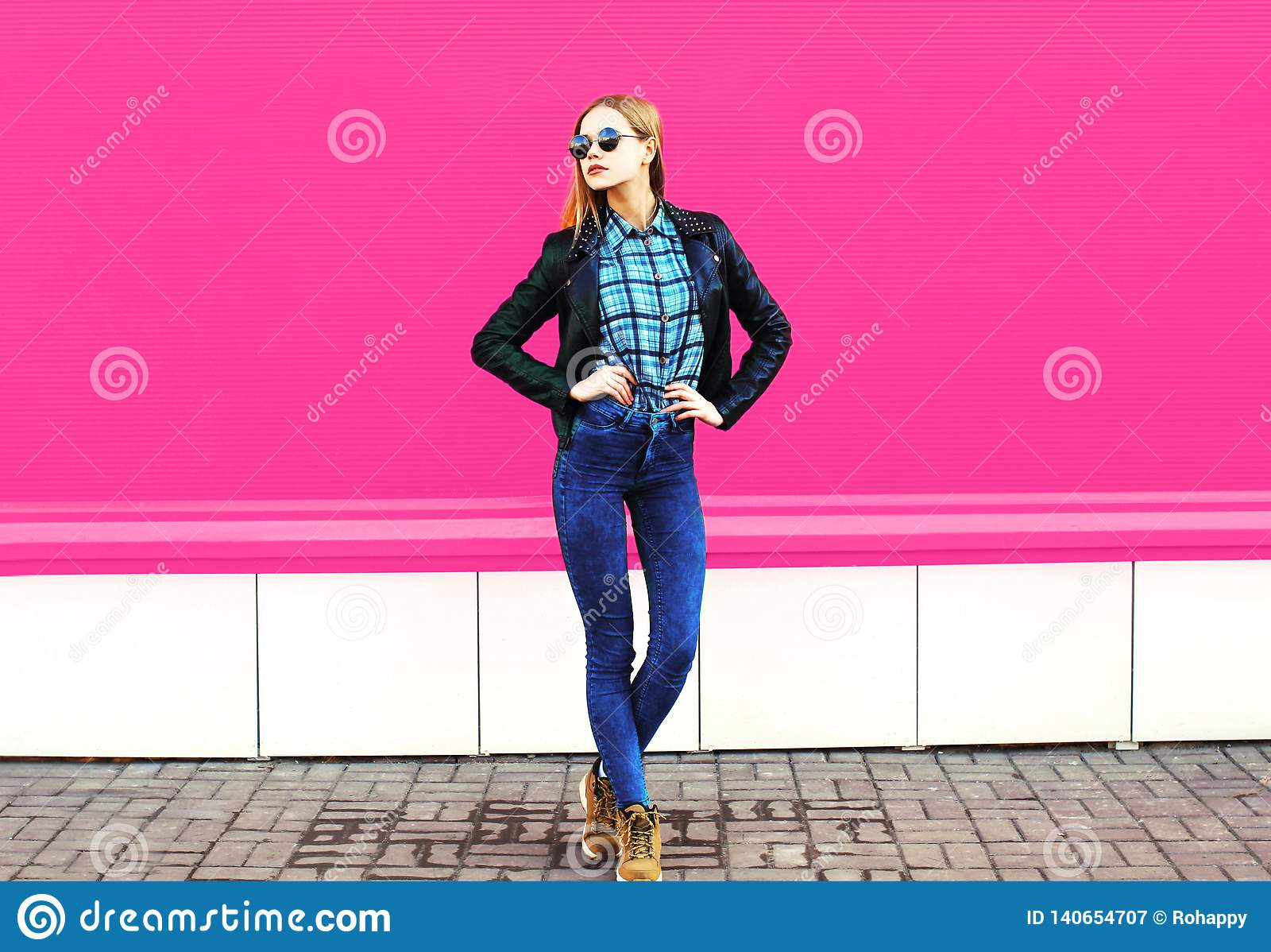 Ładny blondynki dziewczyny model w długiej pozuje jest ubranym rockowej czerń stylu kurtce, kapelusz na miasto ulicie nad kolorow
