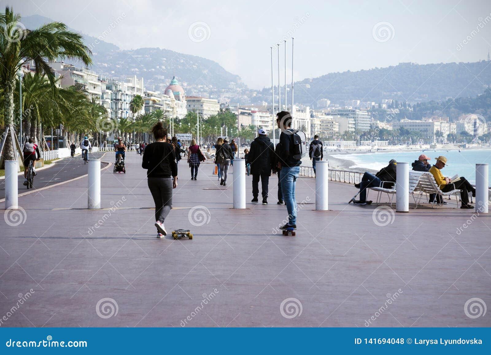 Ładny, Francja, Marzec 2019 Dwa młodzi ludzie: chłopiec i dziewczyna jedziemy deskorolka wzdłuż deptaka Cote d ` Azur