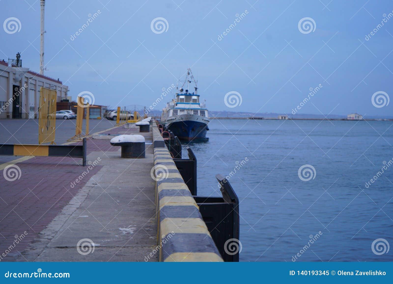 Ładunku statek wiązał dla doku przy portem morskim, plandeka w górę, szeroki kąta widok, słoneczny dzień, niebieskie niebo Łódkow
