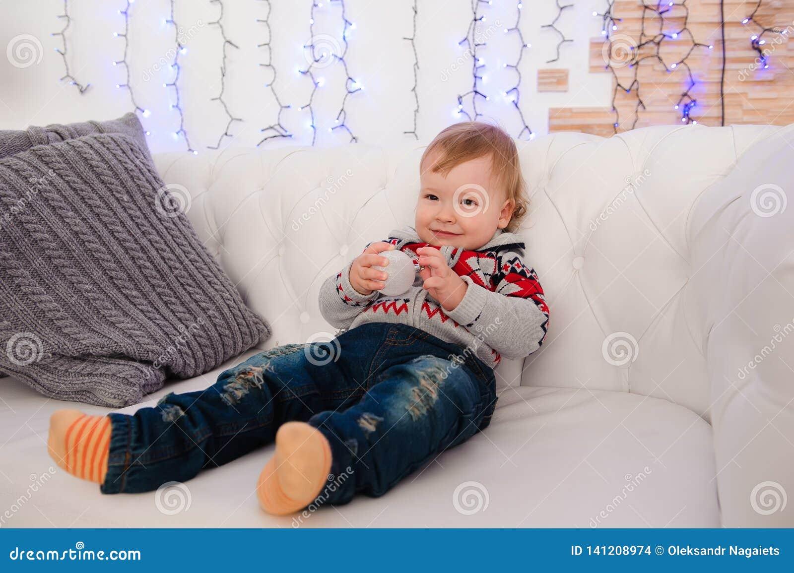 Śliczna chłopiec siedzi na leżance w domu