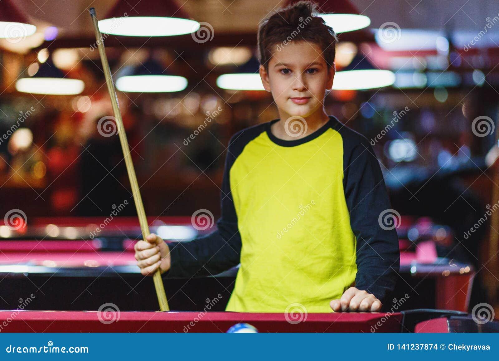 Śliczna chłopiec w żółtych t koszulowych sztukach bilardowych lub basen w klubie Dzieciak uczy się bawić się snooker Chłopiec z b