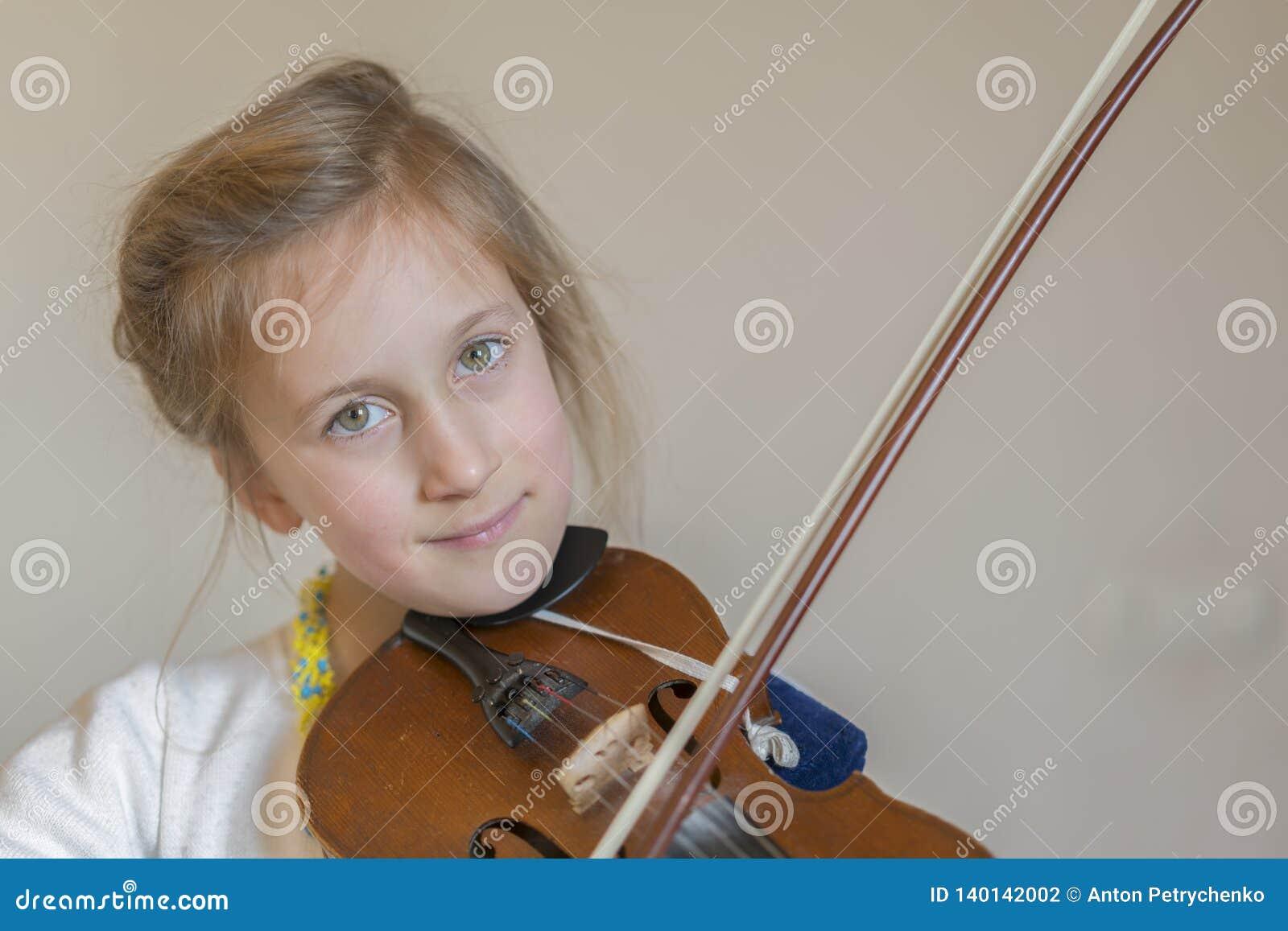 Śliczna mała dziewczynka w pięknym smokingowym bawić się skrzypce Radosne i szczęśliwe emocje szkolenie Edukacja szkoła Estetyczn