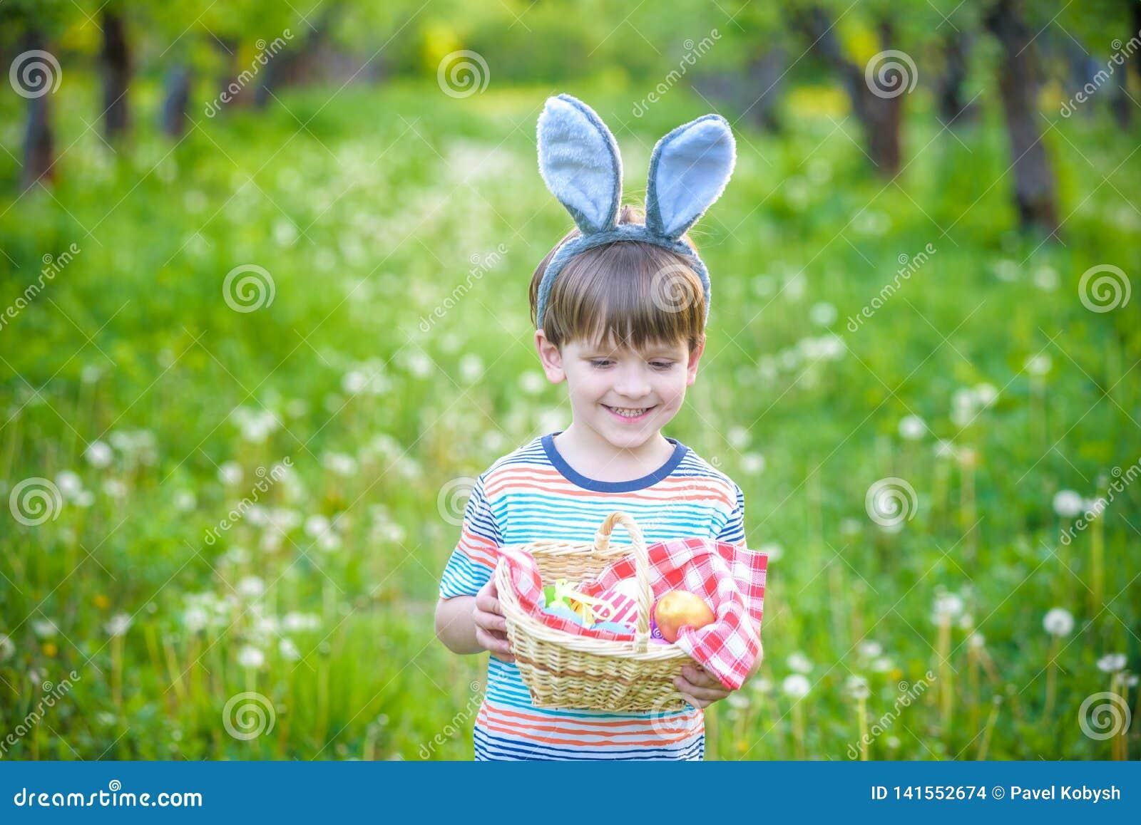 Śliczna małe dziecko chłopiec z królików ucho ma zabawę z tradycyjnymi Wielkanocnymi jajkami tropi