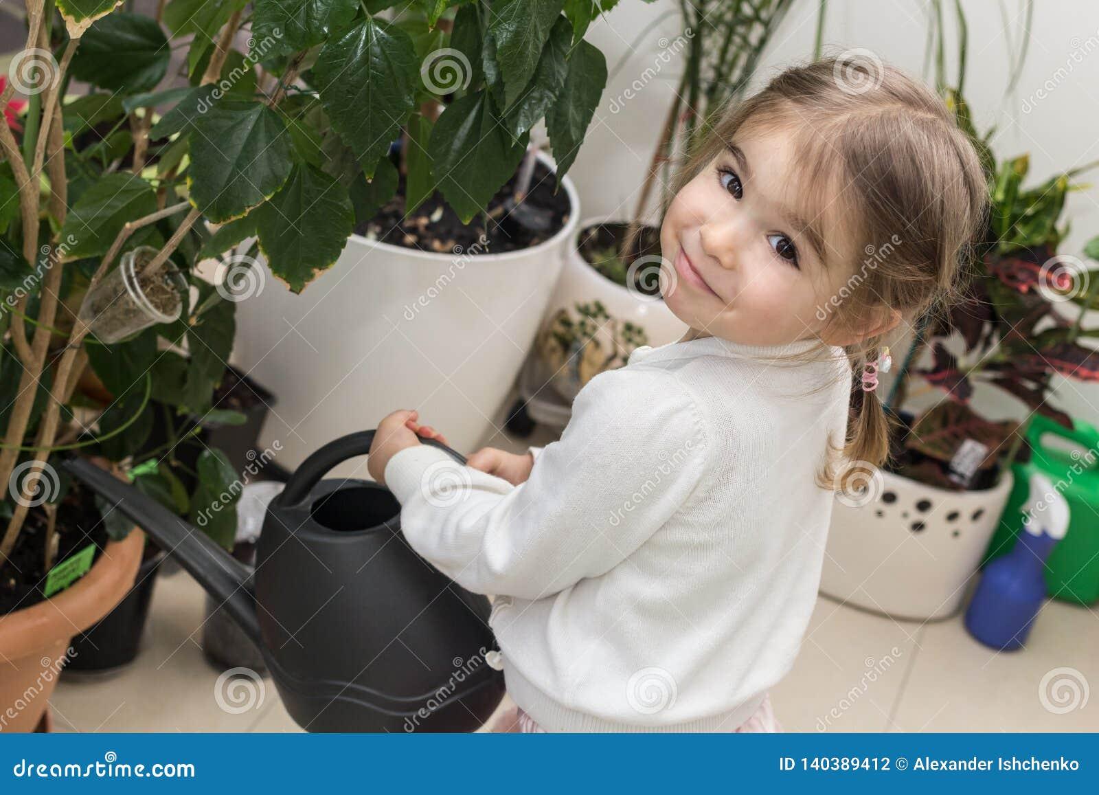 Śliczne małej dziewczynki podlewania rośliny w ona domowa