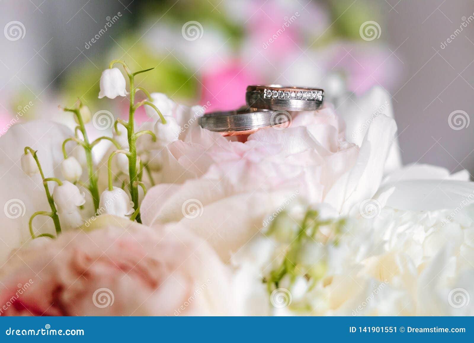Ślubny bukiet z pierścionkami na wierzchołku od bocznego widoku