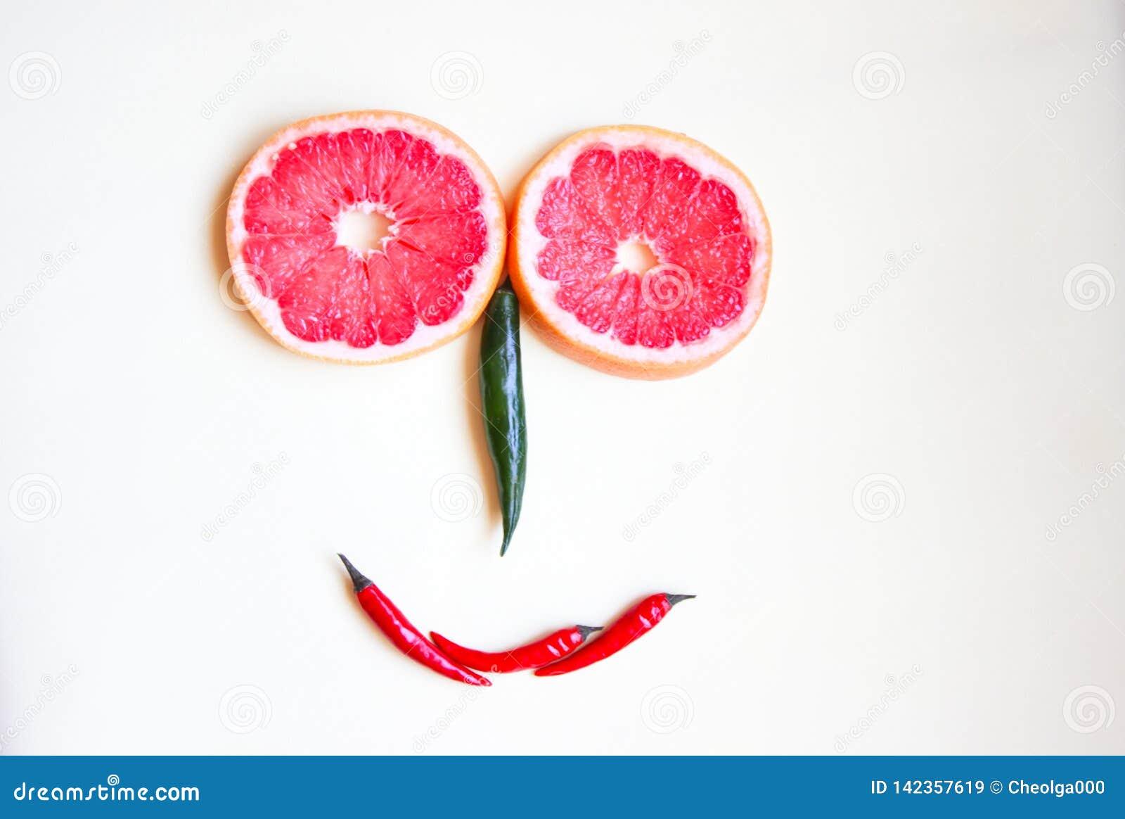 Śmieszna twarz robić owoc i barwiący gorący pieprz