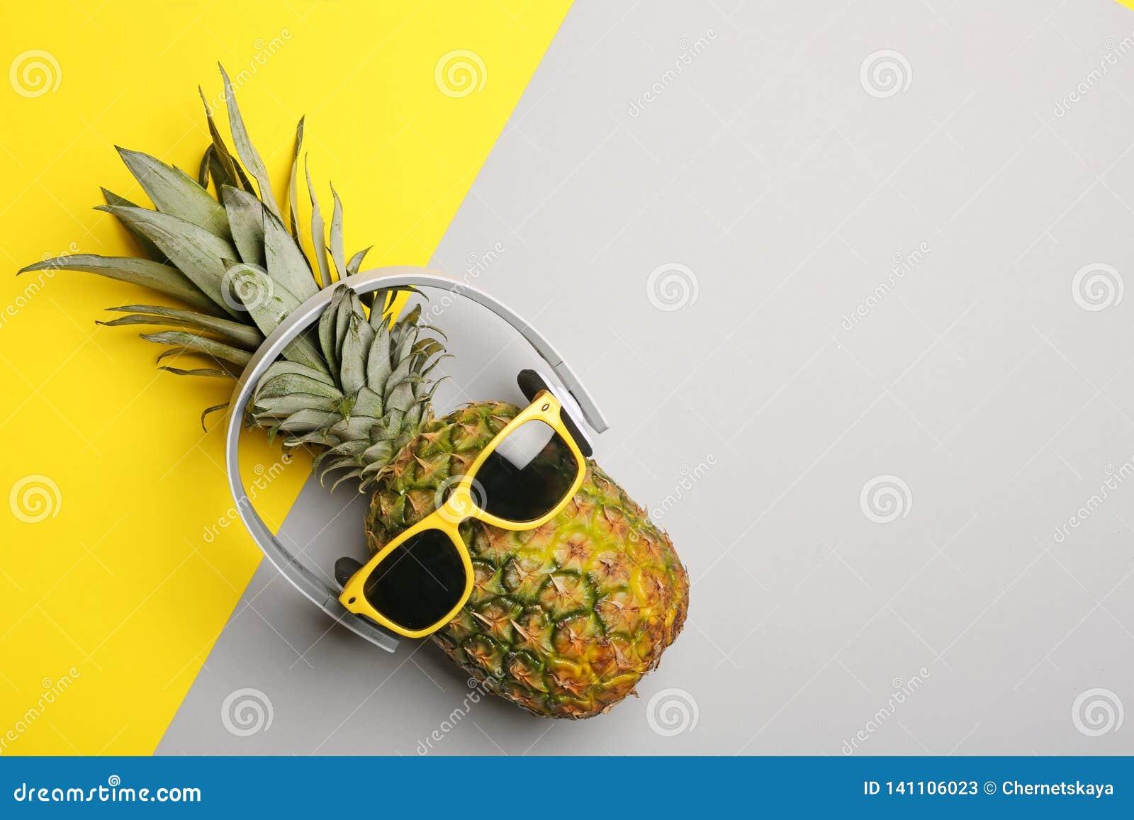 Śmieszny ananas z hełmofonami i okularami przeciwsłonecznymi na koloru tle, odgórny widok
