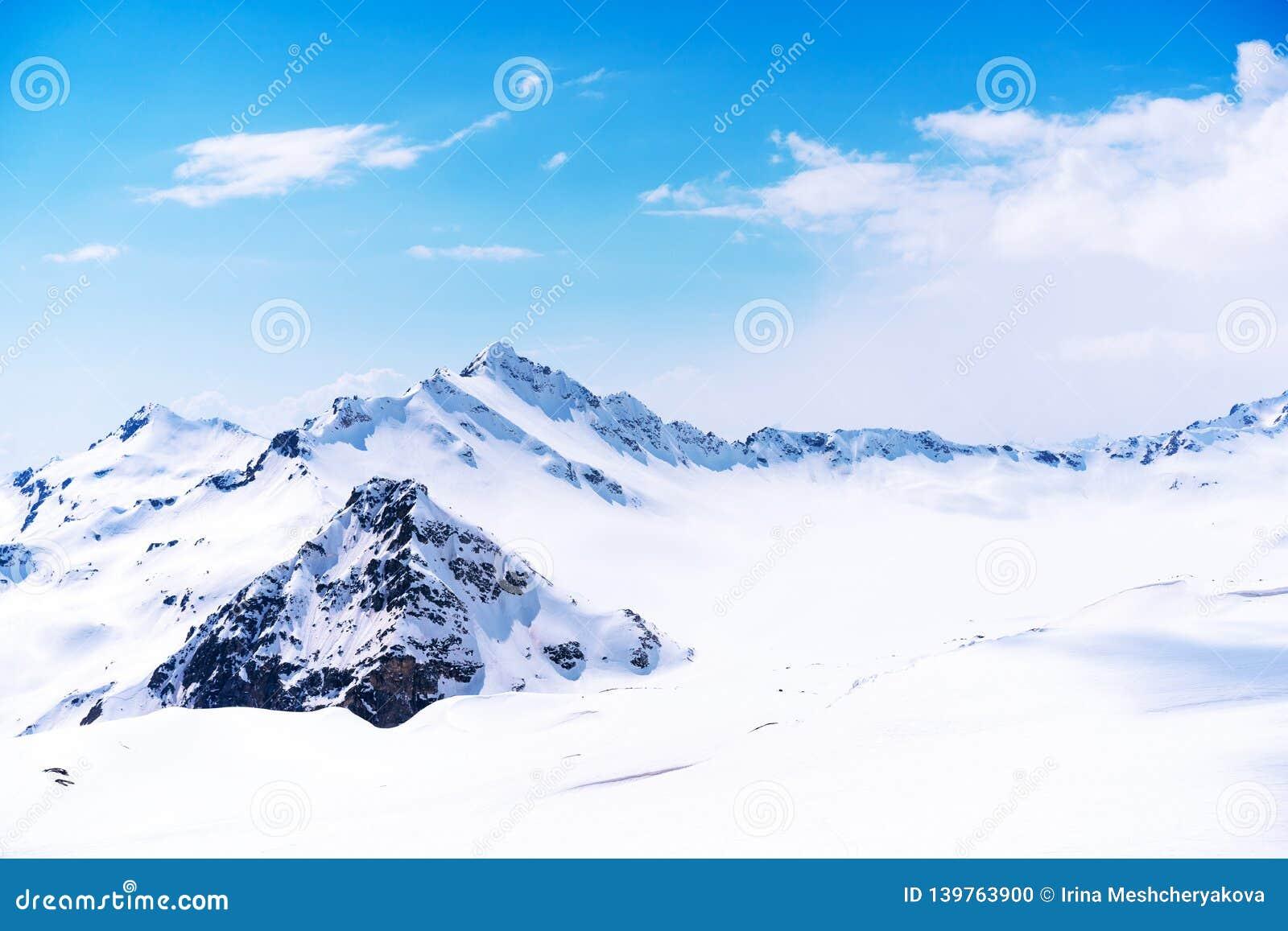 Śnieg nakrywał szczyt Elbrus wysokość pod jasnymi błękitnymi panoramicznymi niebami