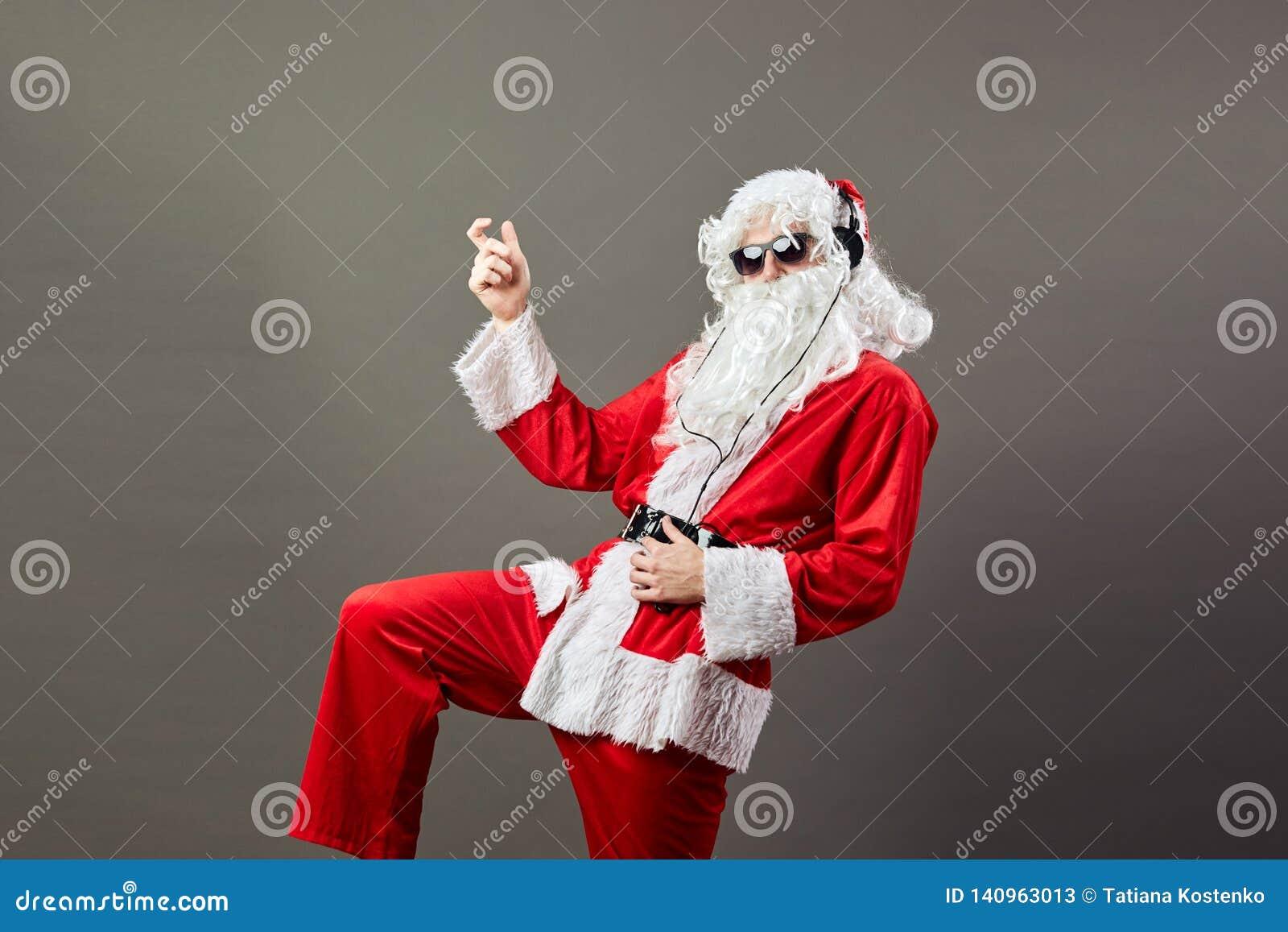 Święty Mikołaj z długą białą brodą w okularach przeciwsłonecznych i hełmofonów tanowie jak kołysamy styl gwiazdę na szarym tle