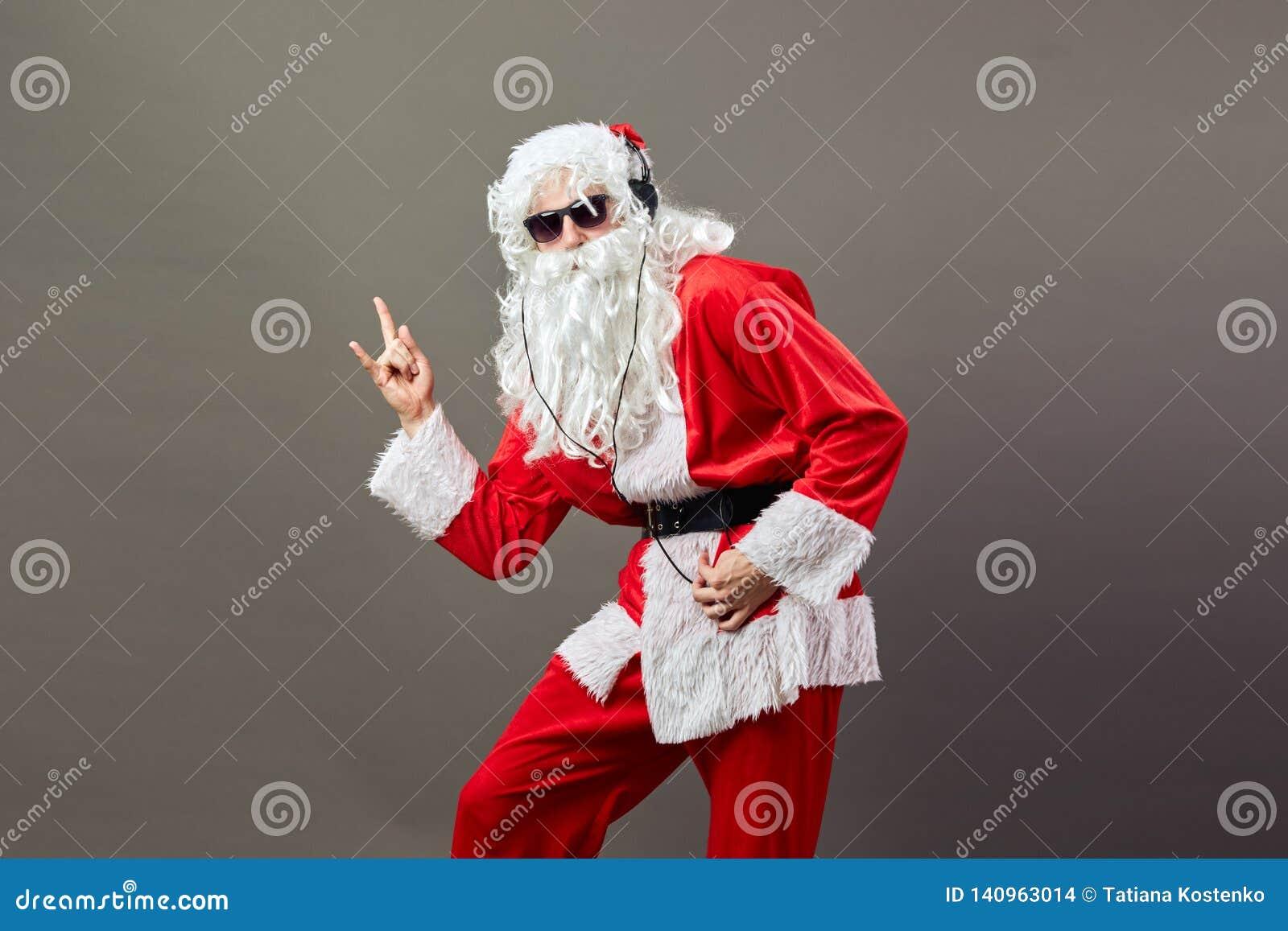 Święty Mikołaj z długą białą brodą w okularach przeciwsłonecznych i hełmofonach pokazuje skała śpiewa na szarym tle
