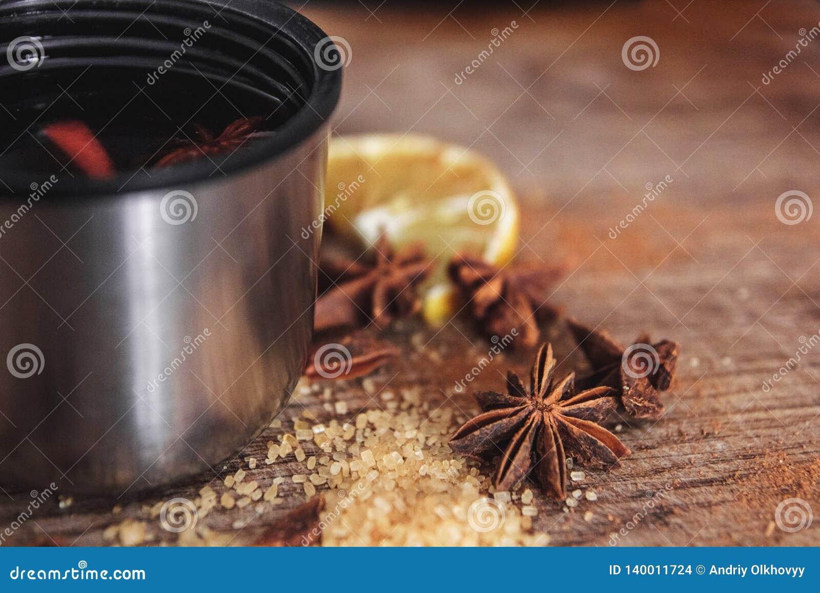Świeżo domowej roboty rozmyślający wino w pucharze z fragrant gatunkami, cytrus owoc, cytryna na drewnianej rusric desce z bliska