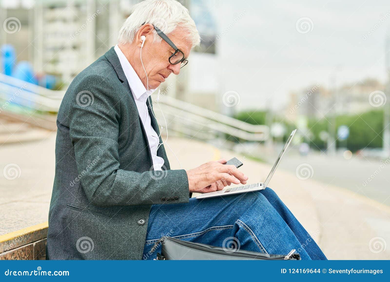 Åldrig affärsman som använder bärbara datorn och lyssnar till musik