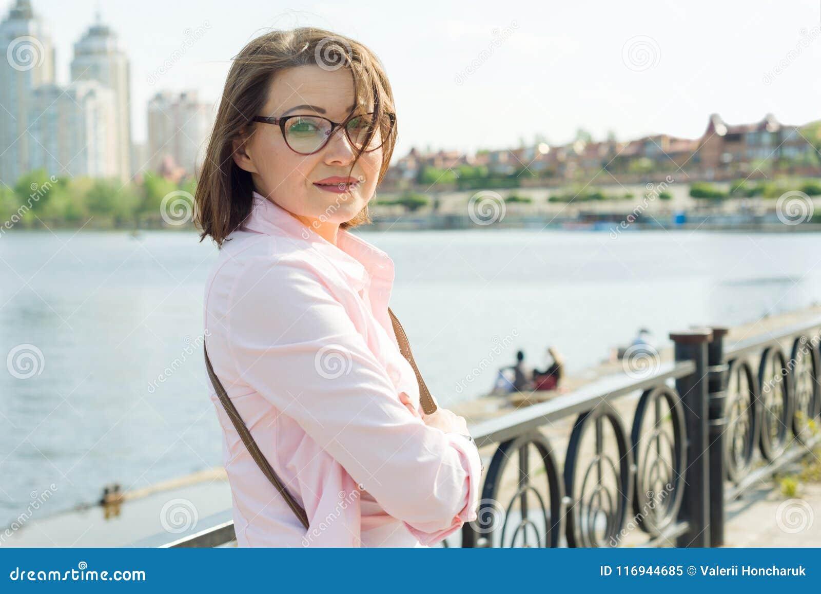 Åldrig kvinna för utomhus- ståendemitt Bakgrundsgata, stad, flod